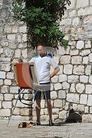 Street artist with an easel and a cat.