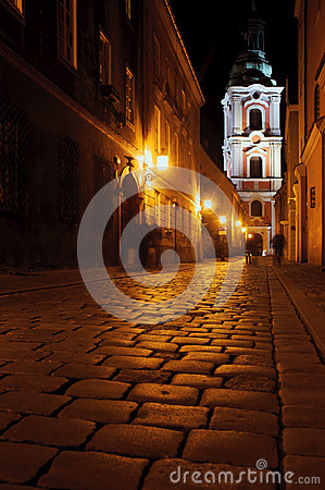 Street with church by night in Poznan