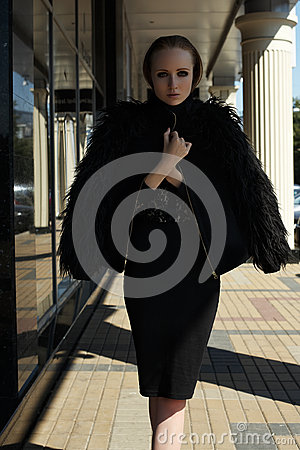 Street fashion style. Beautiful model in chic warm jacket with fluffy fur
