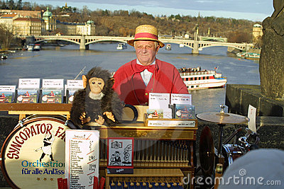 Street organ grinder on Charles Bridge. Prague Editorial Photo