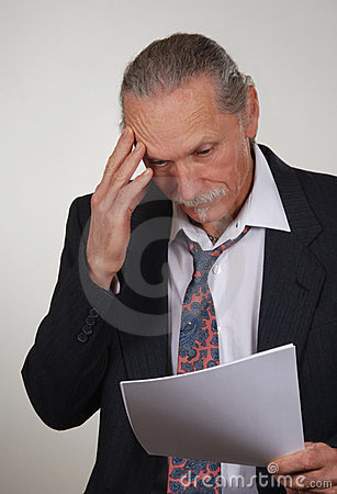 Stressed business man reviewing papers