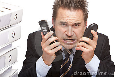 Stressed business man with telephones is crying