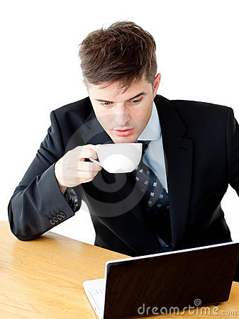 Stressed businessman drinking coffee using laptop