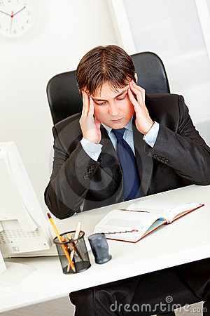 Stressed businessman holding his head and worrying