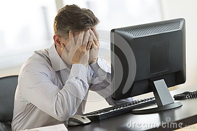 Stressed Businessman Leaning On Computer Desk