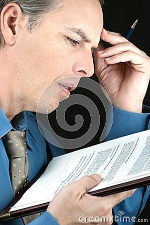 Stressed Businessman Reads Document