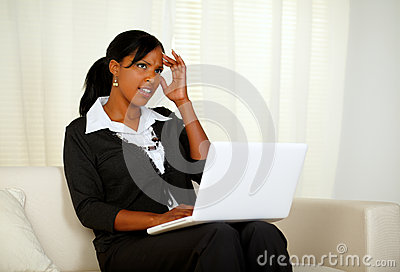 Stressed businesswoman with headache on laptop