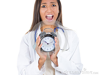 Stressed, overwhelmed female doctor , screaming, holding alarm clock in her hands