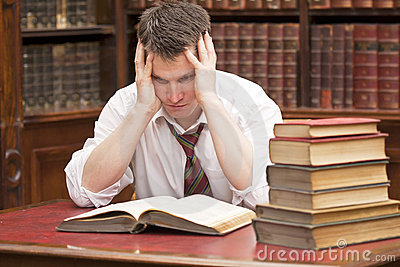 Stressed student with a pile of books to read