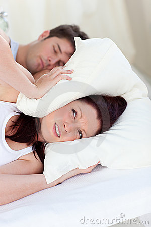 Stressed woman with head under the pillow