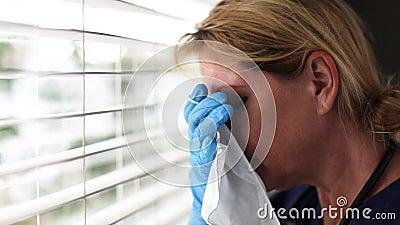 Stressierter Arzt oder Krankenschwester bei einem Abbruch an Fenstern mit chirurgischen Handschuhen, die eine Maske für die mediz stock video