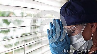 Stresste Ärzte oder Krankenschwestern beim Break-Gebet am Fenster mit Gesichtsmaske und Schutzbrille stock footage
