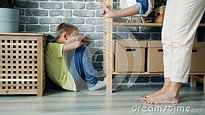 Strikt mor straffar pojken som viftar finger på barn som sitter på golvet och gråter arkivfilmer