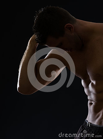 Strong athletic man posing on black