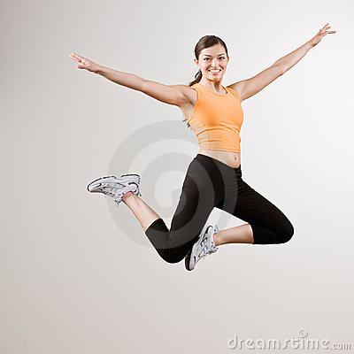Strong athletic woman jumping in mid-air