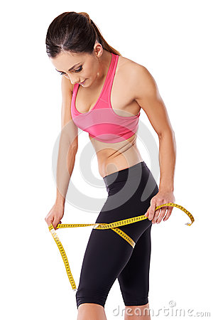 Strong female athlete measuring her thigh
