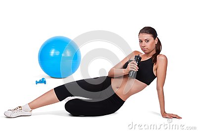 Strong girl lifting dumbbells on fitball