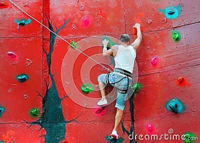 Strong man climbing on a climbing wall