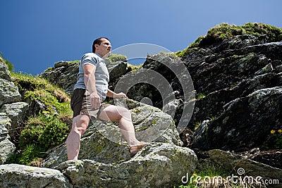 Strong man climbing mountain