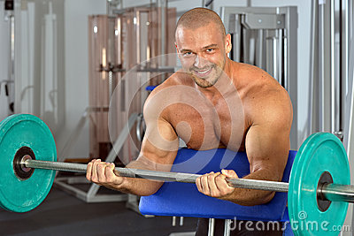 Strong man exercising  with barbell.