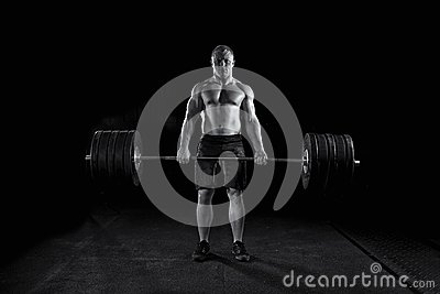 Strong sexy man deadlifts a lot of weight