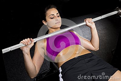 Strong sexy woman bench presses