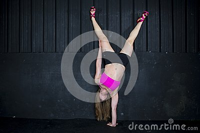 Strong woman one handed handstand