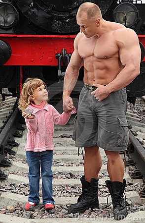 Strong shirtless man stands on railroad with girl