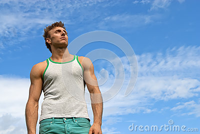 Strong young man on blue sky background