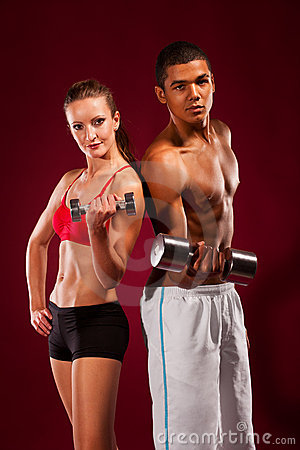Strong young man and woman with dumbbells