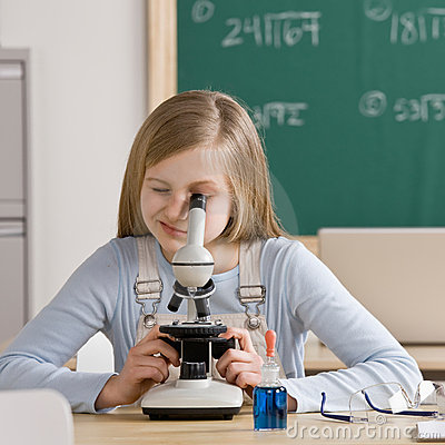 Student in classroom peering into microscope
