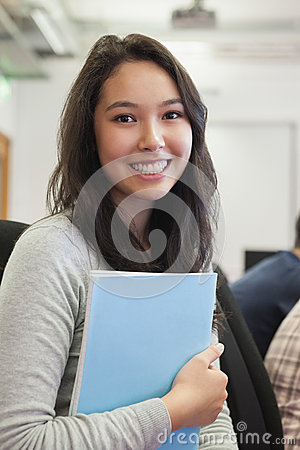 Student in a computer room holding a folder