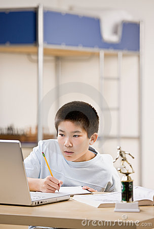 Student doing homework and using laptop