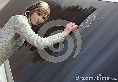 Student erasing the chalkboard/blackboard