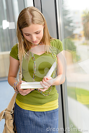 Student girl reading book standing by window