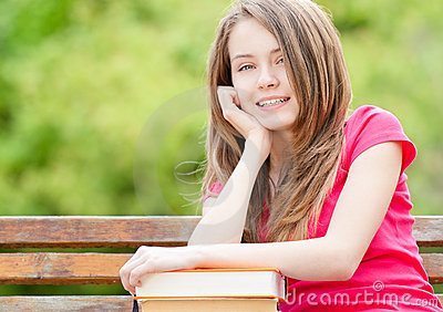 Student girl sitting on bench and smiling