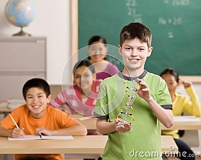 Student holding molecular model in classroom