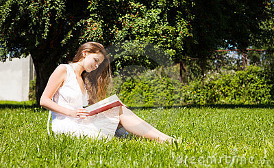 Student sit on lawn and reads textbook