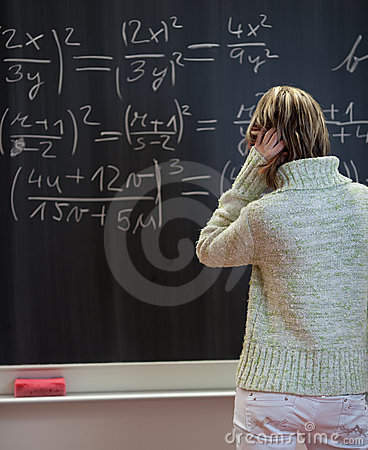Student standing in front of a chalkboard