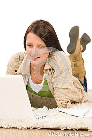 Student teenager girl typing laptop lying floor