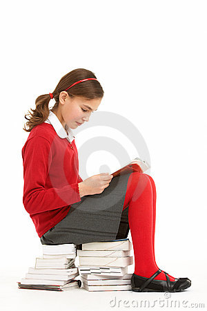 Student In Uniform On Pile Of Books