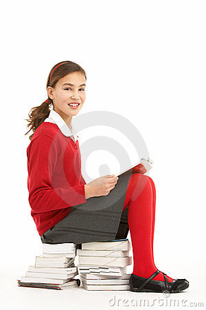 Student In Uniform Sitting On Pile Of Books