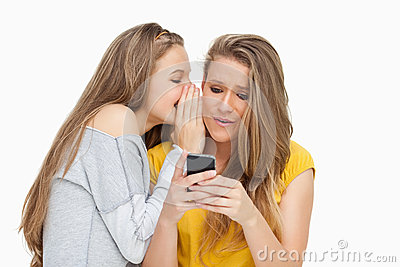 Student whispering to her friend who s texting on her phone