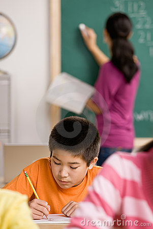 Free Student Writing In Notebook In School Classroom Stock Photography - 6598542