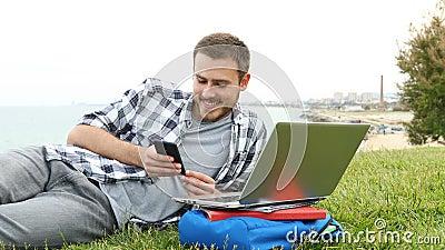 Studente che usa uno smartphone sdraiato sull'erba stock footage