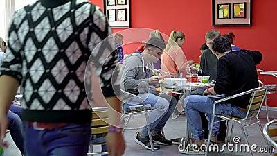 Studenter som har lunch i matsalen stock video