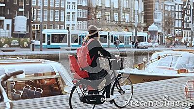 Studentflicka som cyklar cykeln längs en flodkaj Lokal pendlare Kvinnlig i hatten som kryssar omkring på en stadscykel långsam rö lager videofilmer