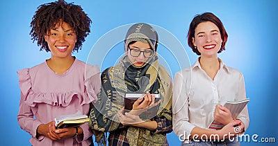 Studenti africani, europei e musulmani con i libri da studiare isolato su un fondo blu Internazionale, sveglio, istruzione stock footage