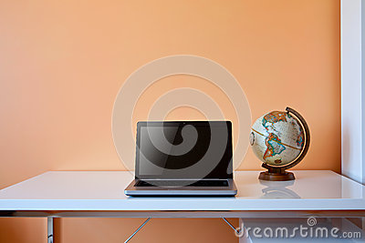 Students desk with globe and laptop