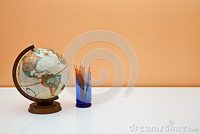 Students desk with globe and pencils